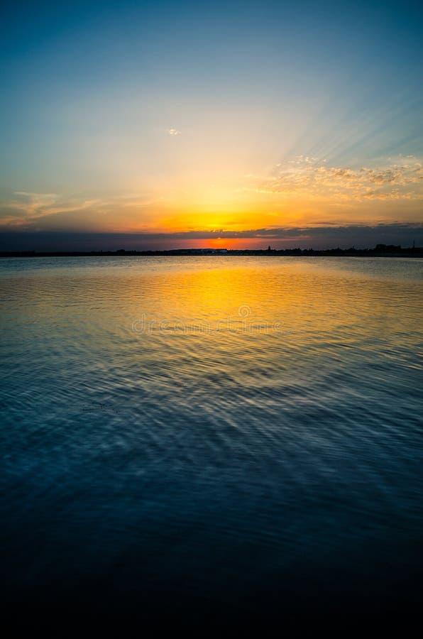 Sun que ajusta-se sobre um lago fotos de stock royalty free