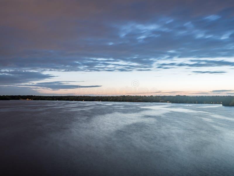 Sun que ajusta-se sobre um lago nas madeiras, no verão imagens de stock royalty free
