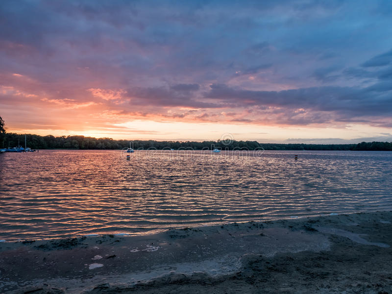 Sun que ajusta-se sobre um lago nas madeiras, no verão foto de stock
