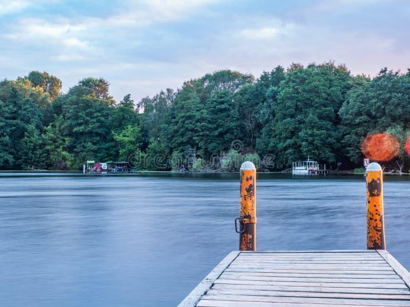 Sun que ajusta-se sobre um lago nas madeiras, no verão foto de stock royalty free