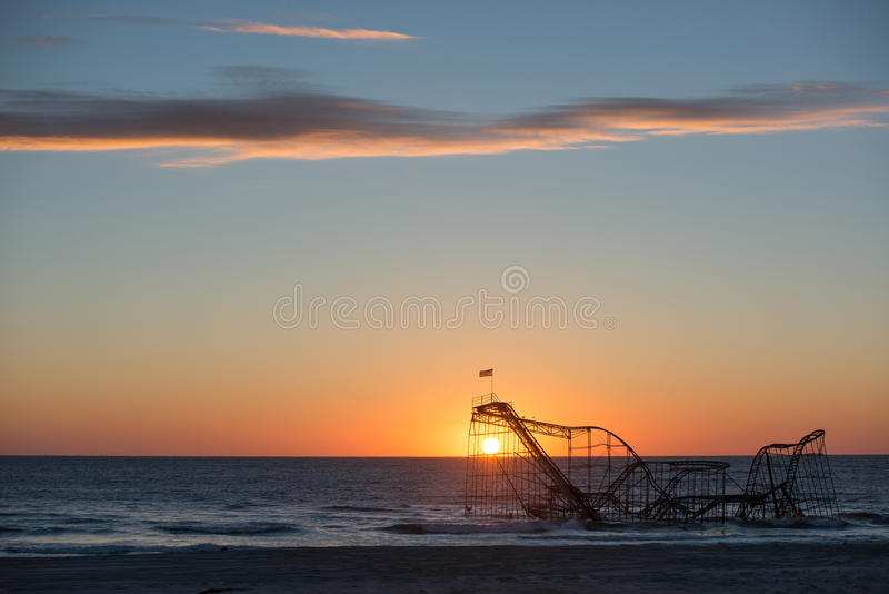 Sun que aumenta atrás de Jet Star Roller Coaster no oceano fotografia de stock royalty free