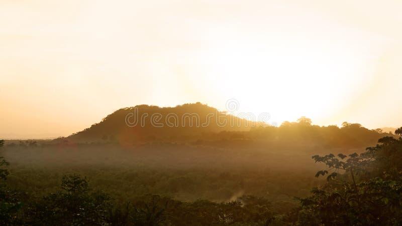 Sun que aumenta atrás de uma montanha no início de uma manhã nevoenta fotos de stock