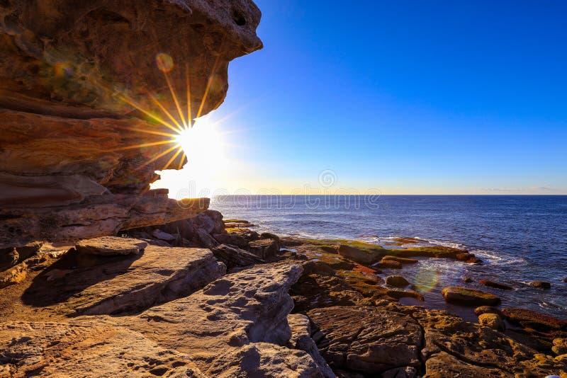 Sun que aumenta sobre o oceano e o céu azul com litoral rochoso imagem de stock