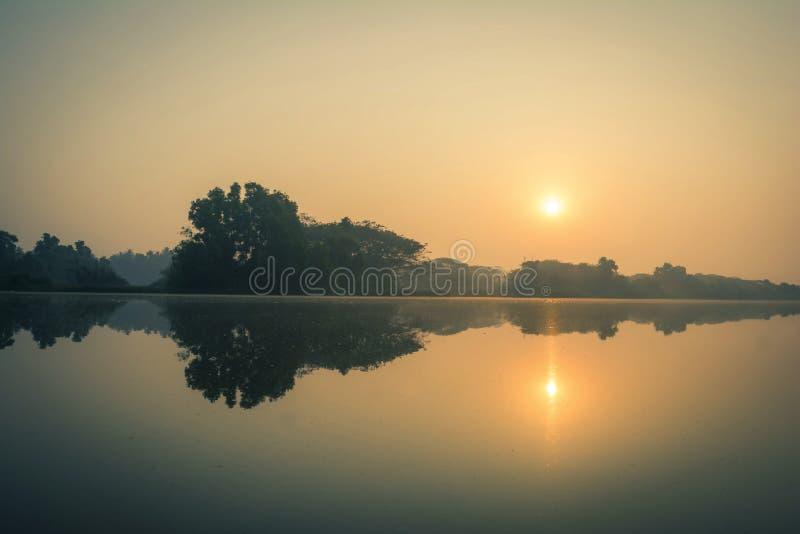 Sun que aumenta sobre um rio calmo foto de stock