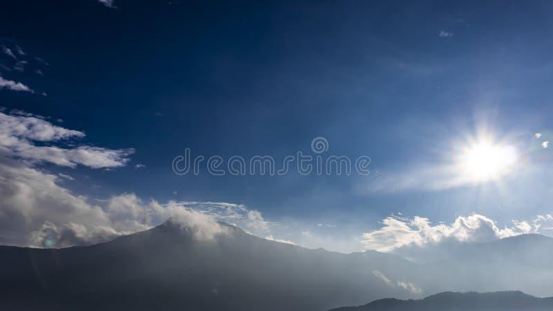 Sun que brilha sobre uma manhã nebulosa da paisagem da montanha fotografia de stock