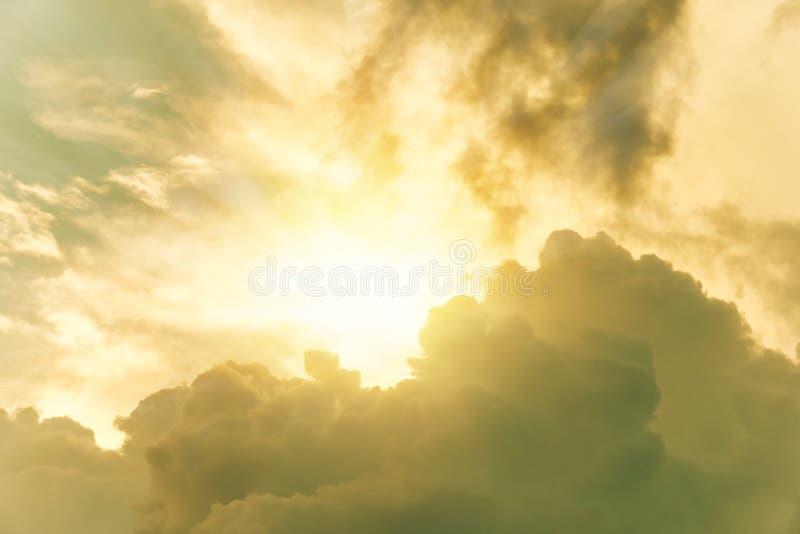 Sun que brilla a través de las nubes dramáticas amarillas en cielo foto de archivo