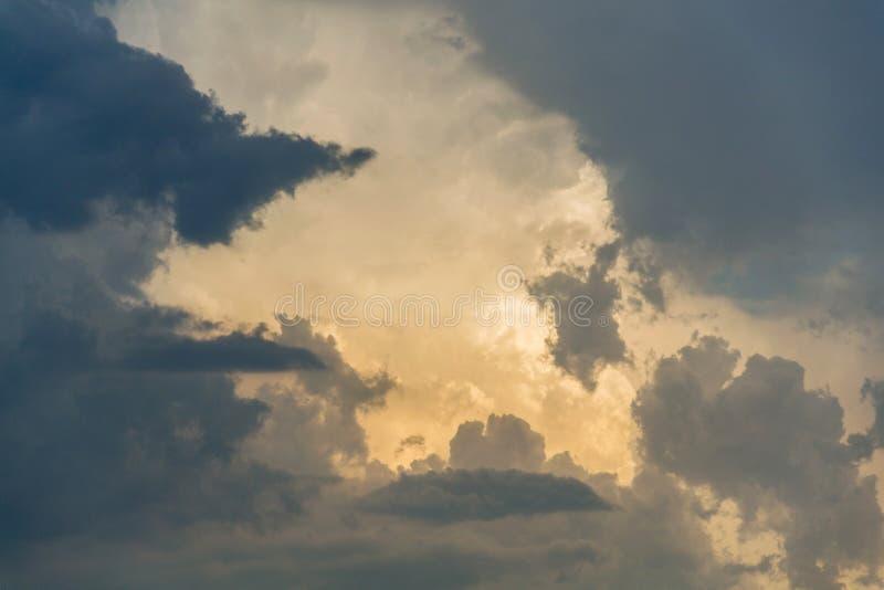 Sun que esconde atrás das nuvens dramáticas durante o por do sol nebuloso temperamental, espaço da cópia, meditação calma foto de stock