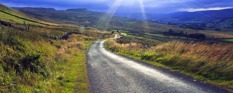 Sun que estalla a través de la nube sobre los valles de Yorkshire del camino lateral del risco imagenes de archivo