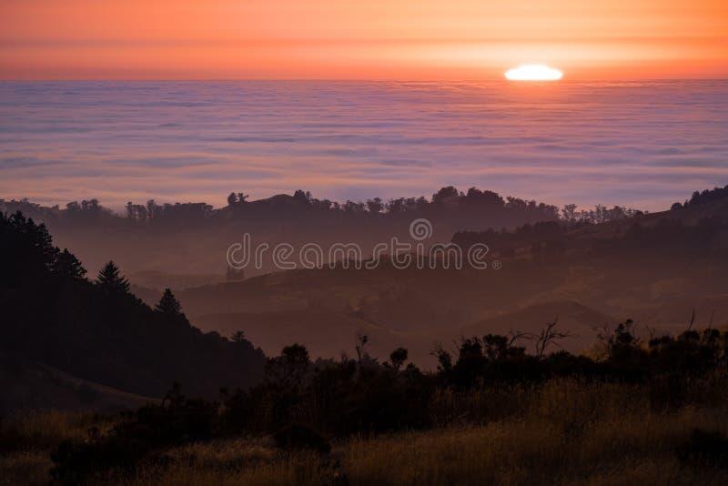 Sun que fija sobre un mar de nubes; colinas acodadas y valles visibles en el primero plano; Montañas de Santa Cruz, San Francisco fotos de archivo