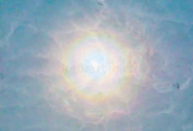Sun que se rompe a través de un cielo muy nublado, luz brillante en colores del arco iris, fenómeno del tiempo en el cielo, esper foto de archivo