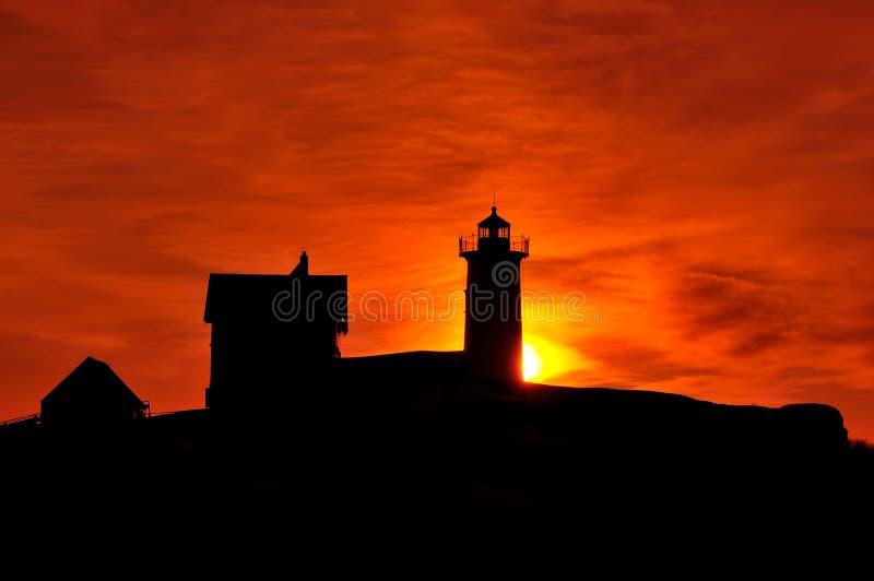 Sun que sube detrás del faro de Neddick del cabo fotografía de archivo libre de regalías