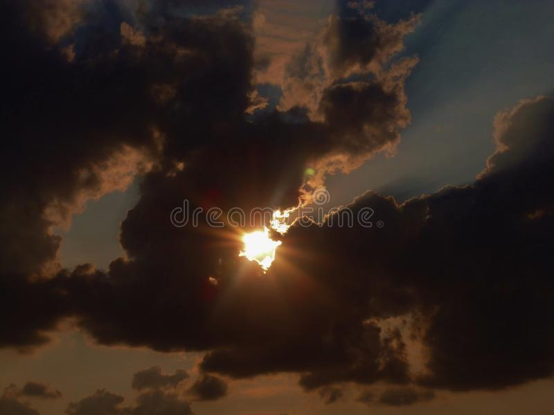 Sun radiating through the clouds. Sunlight passing through the white and grey shadowed clouds with radial starlike radiation and traces of additional colours stock image