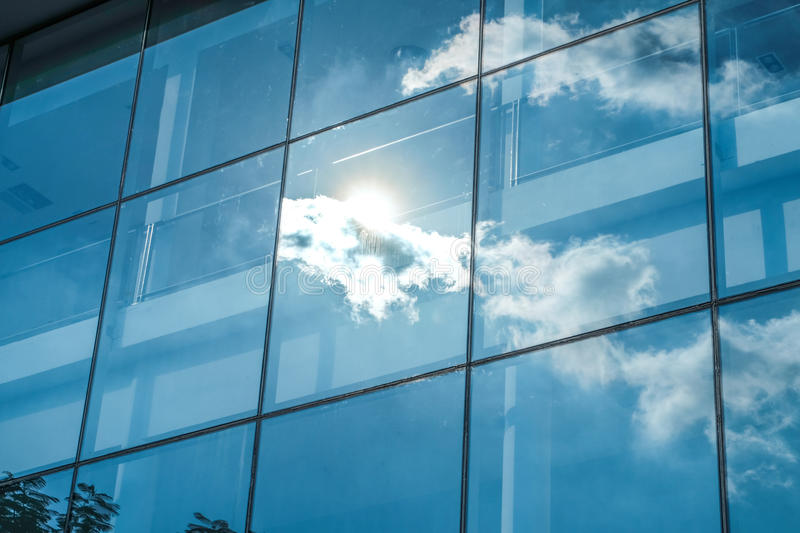 Sun ray and blue sky reflection on window office building, Business concept royalty free stock photo