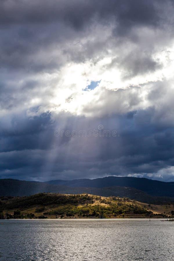 Sun rayonne briller par des nuages sur les collines du lac Jindabyne, photo stock