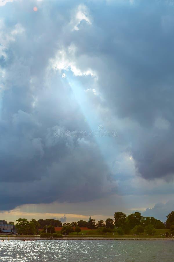 Sun rayonne briller par le ciel nuageux foncé photographie stock