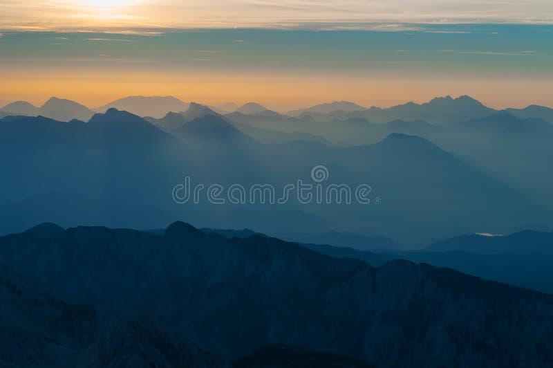Sun rayonne les gammes de montagne illuminating par la brume de matin photographie stock libre de droits