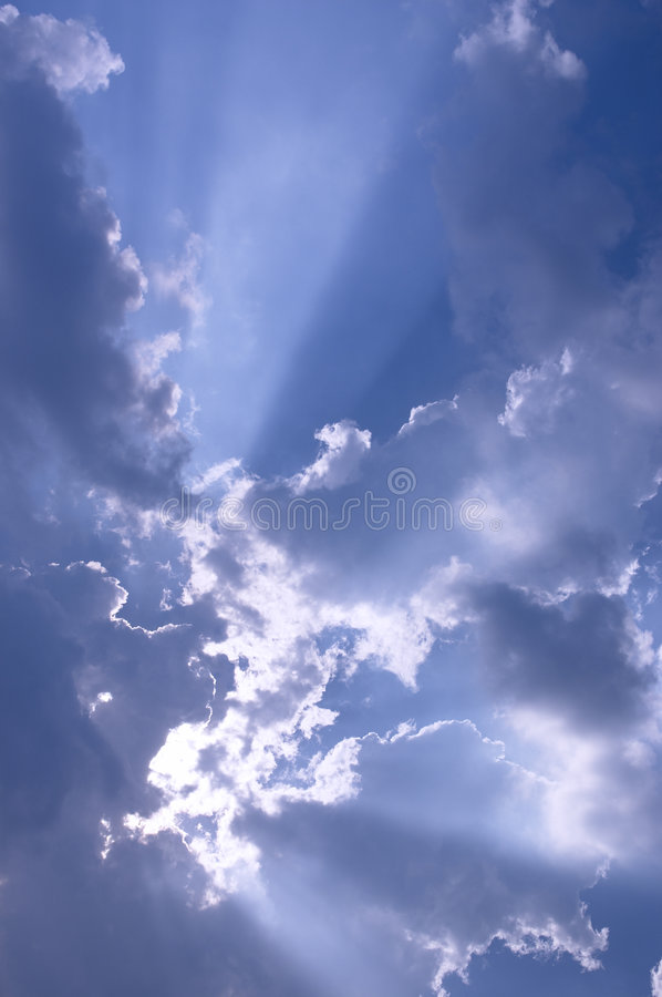 Sun Rays. Bursting from behind white clouds and blue skies