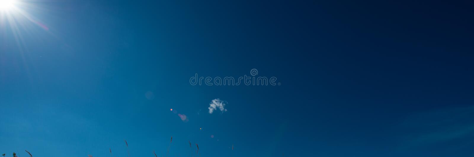 Sun rays against the blue sky with a small cloud. Web banner royalty free stock images