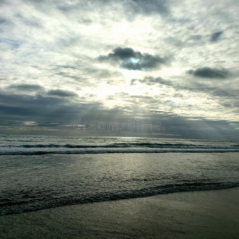 Sun rays on beach rolling waves horizon line. Sand, water, vacation, sky, blue, wet, rolling, clouds, summer, rain, horizon, pacific, sea, fun, lifestyle royalty free stock photo