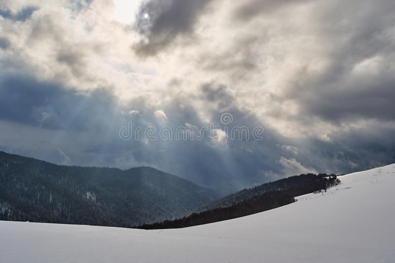 Sun rays breaking through the clouds in Winter, above a forest and a snow covered mountain, at Baiului mountains Carpathians. Sun rays breaking through the stock photo