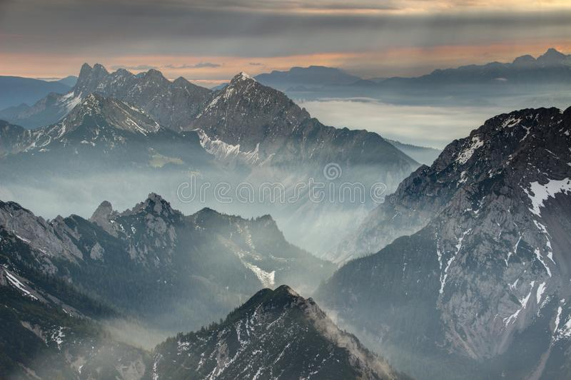 Sun rays burst through dark clouds over jagged Karavanke range. Sun rays burst through dark grey clouds over jagged hazy Koschutnikturm Kosutnikov Turn peaks of stock images