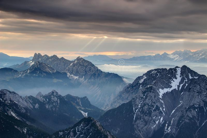 Sun rays burst through dark gray clouds over misty jagged peaks. Sun rays burst through dark grey cloud cover over misty jagged Koschutnikturm Kosutnikov Turn stock photos