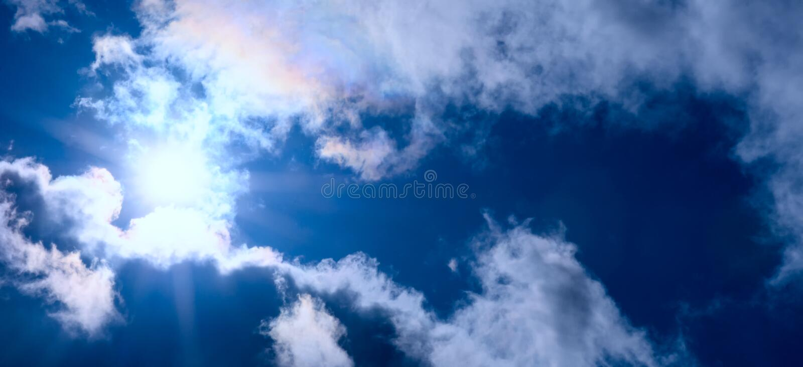 The sun with rays comes out from the edge of white clouds. Concept - God`s blessing, happiness, fullness of life stock image