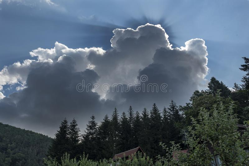 Sun rays coming from under the dark storm clouds above the black forest and roofs of houses stock images