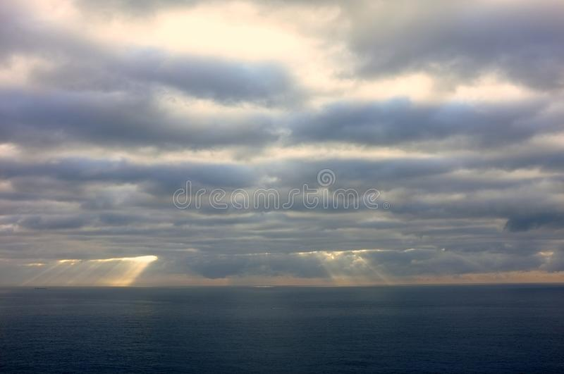 Sun Rays Creeping Through Dense Morning Clouds over Ocean. Dense dark morning clouds over Pacific Ocean, with light rays showing at bottom of cloud bank stock photos