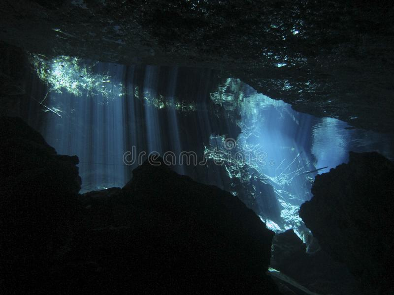 Sun rays entering the water in an underwater cave. Reflection of light - Underwater at cenote Chac Mool in the Riviera Maya, Mexico stock photography