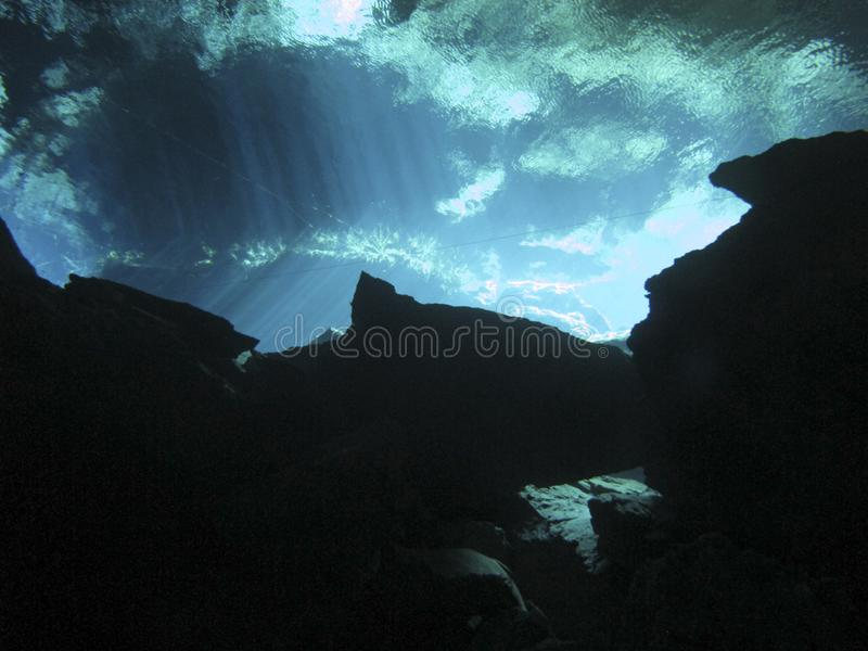 Sun rays entering the water in an underwater cave. Reflection of light - Underwater at cenote Chac Mool in the Riviera Maya, Mexico royalty free stock images