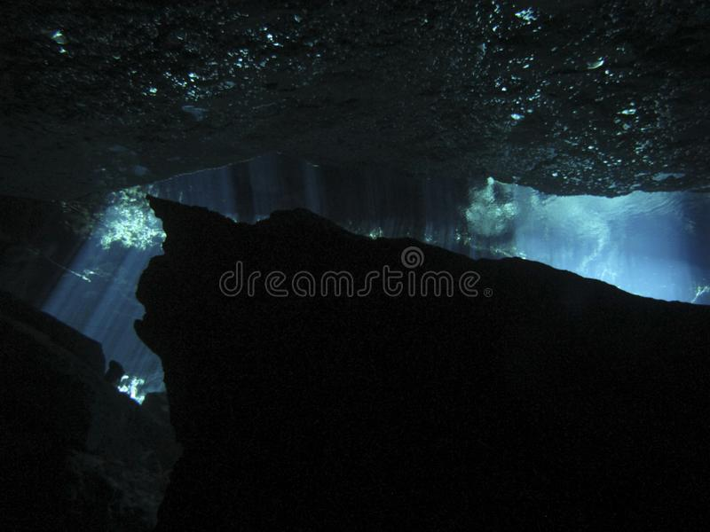 Sun rays entering the water in an underwater cave. Reflection of light - Underwater at cenote Chac Mool in the Riviera Maya, Mexico stock image