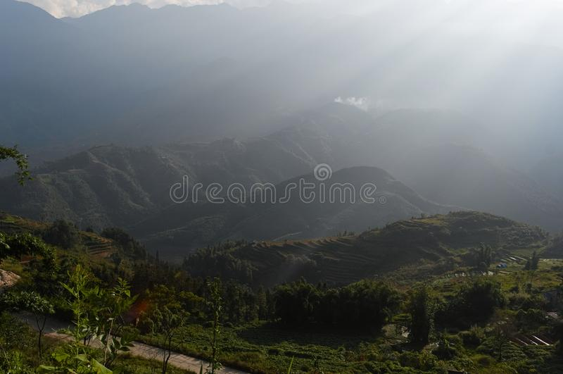 Sun rays over valley with rice terraces and fields stock photos