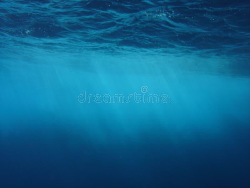 Sun rays penetrating the ocean's surface royalty free stock photos