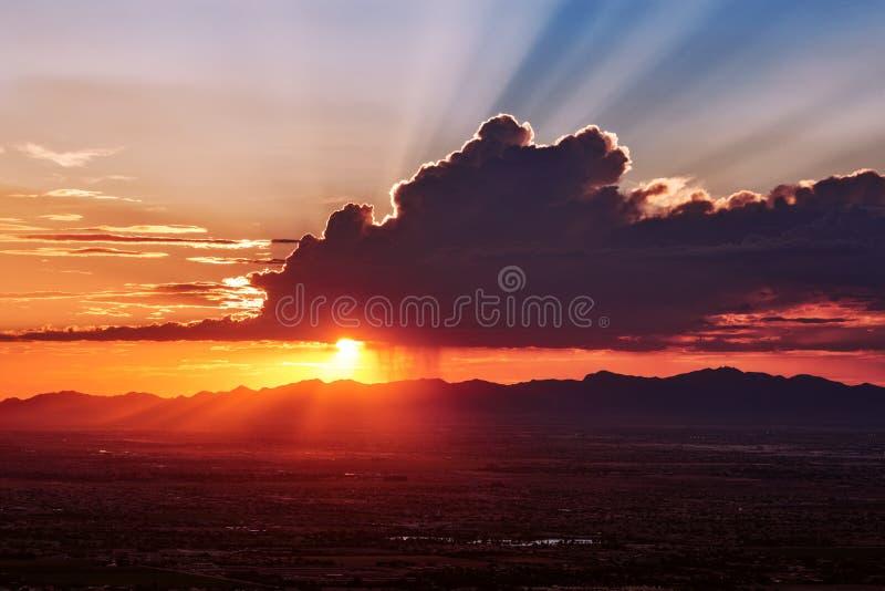 Sun rays shine behind a cumulus cloud at sunset. Sun rays shining from behind a cumulus cloud over Phoenix, Arizona at sunset royalty free stock photos