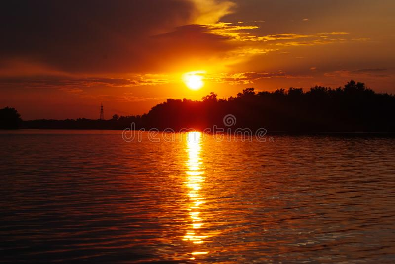 The sun is reflected on the waves, warm summer evening, romantic landscape, bright sunset on the river, royalty free stock image