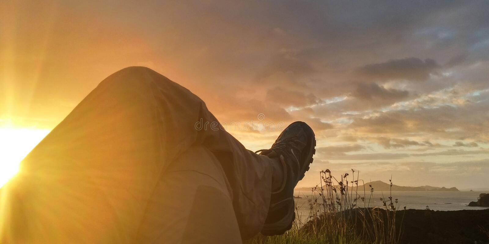 Sun Reflecting on Person Cross Leg Under Cumulus Clouds during Sunrise royalty free stock photo