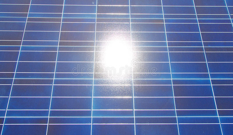 Sun Reflecting in PV panel. The bright sun reflecting in a solar panel royalty free stock image