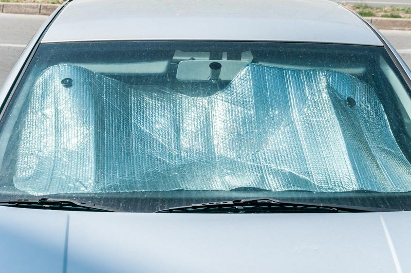 Sun reflector on the windscreen or windshield as protection of the car plastic indoor panel from direct sunlight and heat stock photo