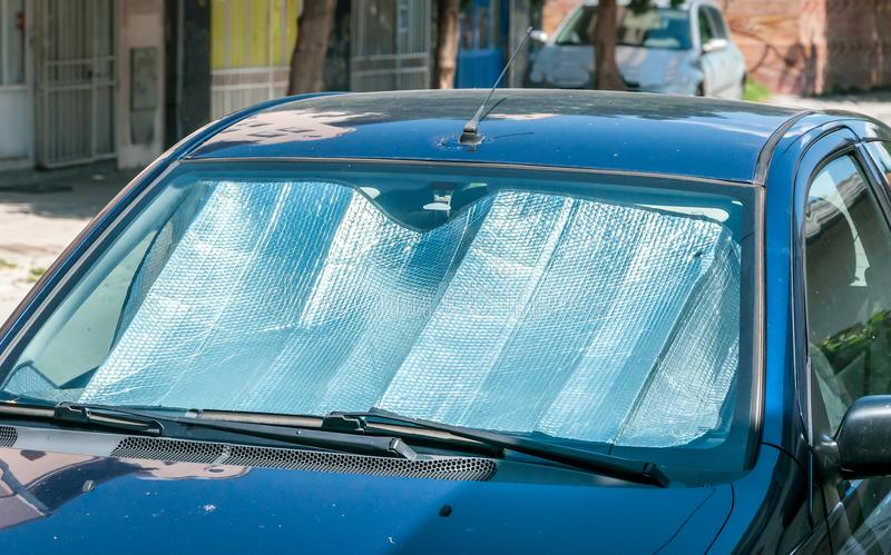 Sun reflector on the windscreen or windshield as protection of the car plastic indoor panel from direct sunlight and heat.  stock image
