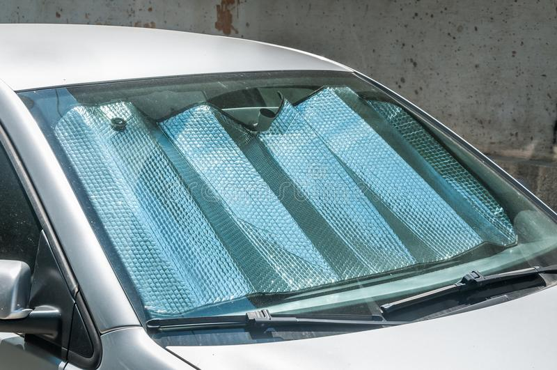 Sun reflector on the windscreen or windshield as protection of the car plastic indoor panel from direct sunlight and heat.  stock photography