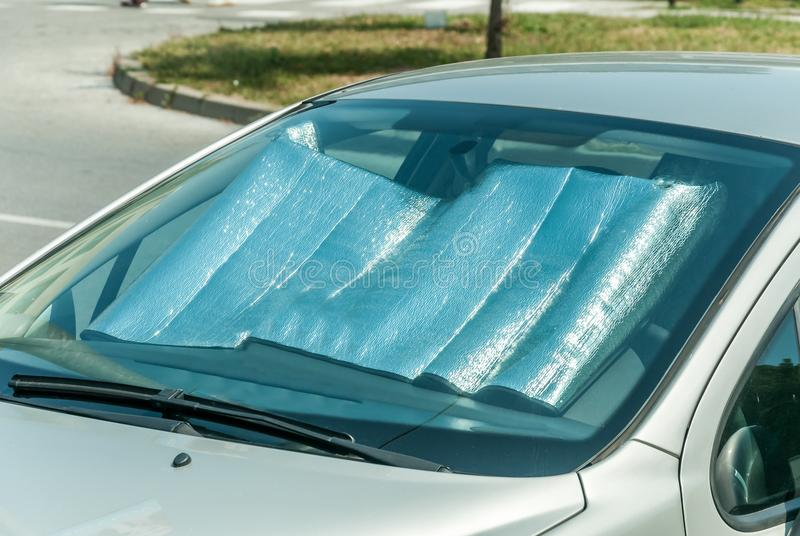 Sun reflector on the windscreen or windshield as protection of the car plastic indoor panel from direct sunlight and heat.  stock photo