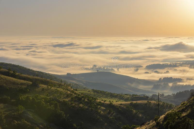 The sun rise above the clouds in the valley stock photo