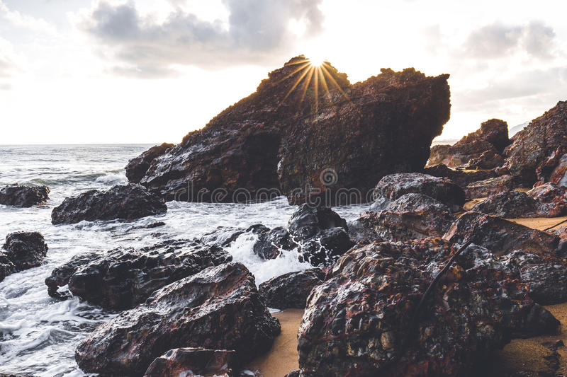 The sun rise behind the rock creating a beautiful star burst effect. stock photos