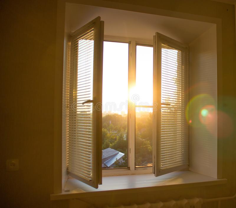 sun rise behind the window blinds and curtains shades stock photo
