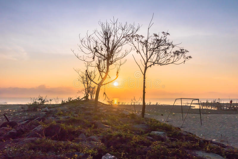 Sun rise obove the Trees on the rock near the dock. Smoke from burning forest from Indonesia. make the light of the sun can fade the sun is red round before royalty free stock photos