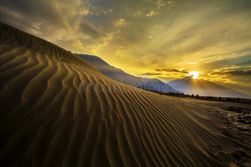 Sun rise at sand dunes against the background of distant colorful mountain range and sunrise sky, Ladakh, Himalaya, Jammu & stock image