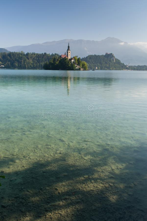 The sun rises above Lake Bled on a clear day. The mountains are visible behind the church on the island royalty free stock photography