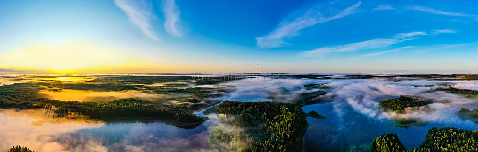 Sun rises on horizon, panoramic landscape. Beautiful morning in green forest near lakes. Environment concept stock photos