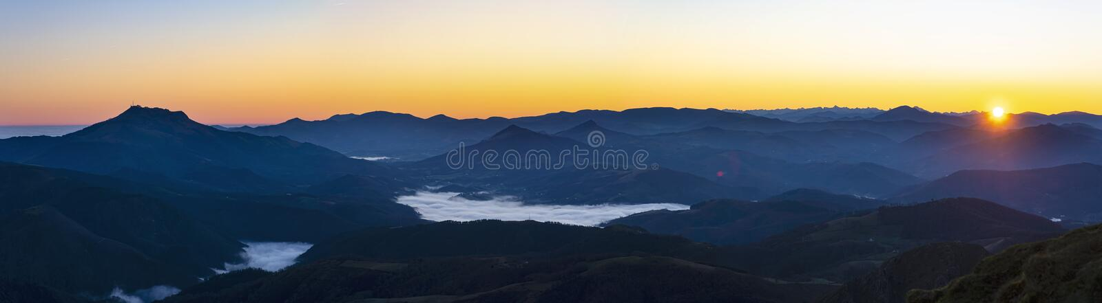 The sun rises with mists over the Pyrenees mountains in Euskadi and Navarra, from the Aiako Harriak Natural Park stock photo